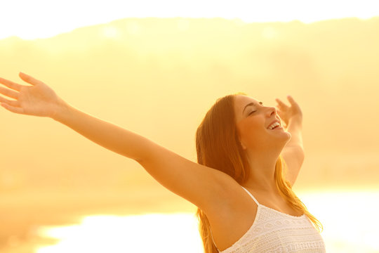 Happy woman trstching arms breathing fresh air at sunset