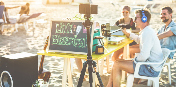 Group of happy people making a video feed online at beach party - Speaker and friends starting live social streaming - New media trends and vlogging concept - Focus on tripod smartphone