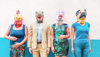 Crazy people wearing chicken, unicorn, dog and t-rex party mask - Trendy people having fun together - Bizarre and funny trend concept - Focus on faces