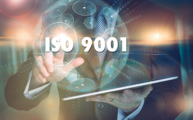 A hand selecting a ISO 9001 business concept on a futuristic computer display.