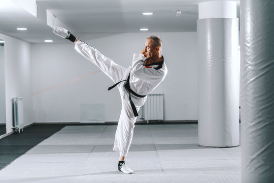 Caucasian trainer in dobok kicking with one leg in gym. Taekwondo class concept.