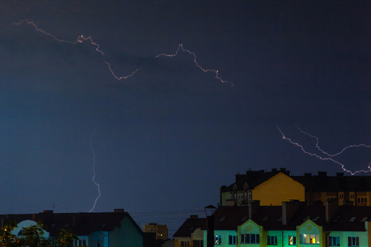 a flash of lightning in the night sky over the city