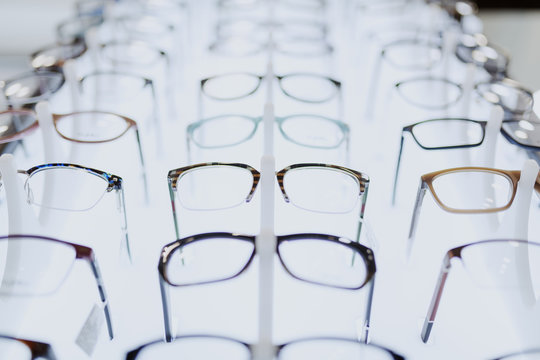 Picture of many different eyeglasses on rack.
