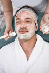 Spa therapy for young man receiving facial mask at beauty salon.