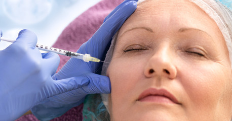 Senior lady having botox injecting procedure