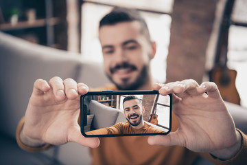 Close-up portrait of his he nice attractive cheerful cheery glad positive bearded guy taking making selfie holding camera in hands at industrial loft interior style living-room