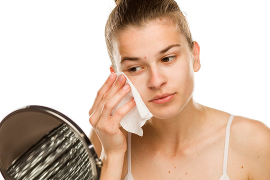 Young woman cleaning her face with wet wipe on white background