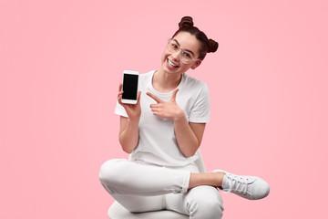 Cheerful teenager presenting smartphone
