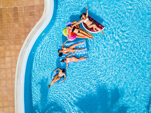 Coloured aerial background group of friends woman caucasian people enjoying the summer holiday vacation at the blue water pool with trendy inflatable mattress lilos together with fun and happiness
