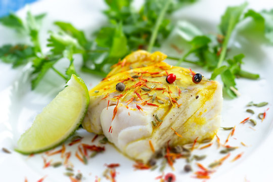 Plate of Steamed fish with saffron spice with salad