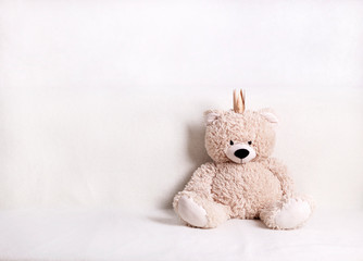 Children's toys - bears of brown and beige color with golden little crownsс are sitting on the sofa. Selective focus.