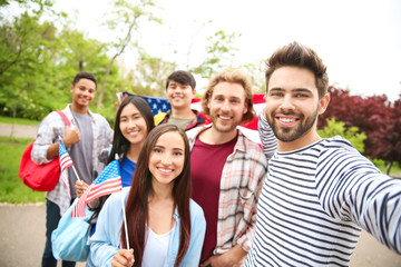 Group of students with USA flag taking selfie outdoors