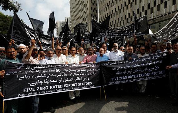 Businessmen and traders carry black flags and banners against the proposed imposition of sales tax on export industry, during a protest in Karachi