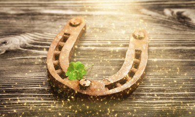 Metal horseshoe and cloverleaf on wooden table
