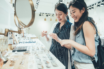 two asian women customer in busy clothes shop shopping accessories taking up from table. beautiful smiling young ladies best friends buying choosing earrings on desk in fashion modern store tokyo