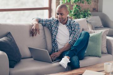 Portrait of positive cheerful satisfied man student have modern technology use user dressed denim jeans plaid shirt look screen sit divan big apartment  Papier Peint