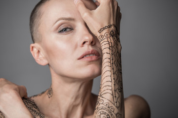 Skinhead woman portrait with mehendi on an arm