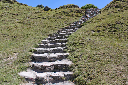 Stone steps cut into a grassy bank lead up the hillside to the summit.