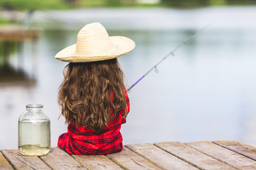 Cute little child girl in rubber boots and straw hat fishing from wooden pier near glass jar and little fish on a lake. Family leisure activity