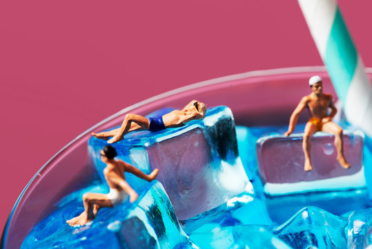 miniature men in swimsuit on a cocktail