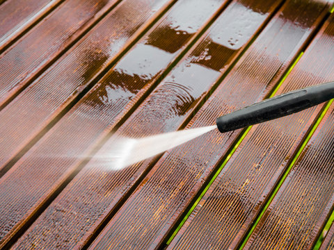 Close up view of using pressure washer to clean impregnated wood terrace outdoors in the spring.