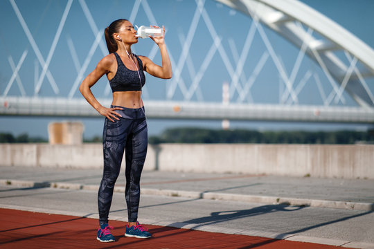 Young woman resting after jogging and drink water on a sunny day