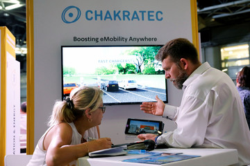 People chat at Israeli energy storage firm Chakratec's exhibition stall at EcoMotion conference in Tel Aviv