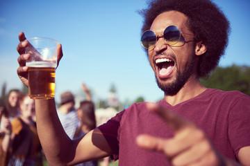 Photo sur Plexiglas Magasin de musique Screaming African man drinking beer at the music festival