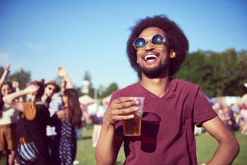 Happy African man drinking beer in festival