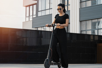 Young attractive woman riding electrick kick scooter at modern cityscape.