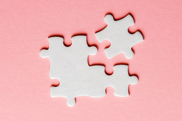 Wall Mural - White details of puzzle on a pink background
