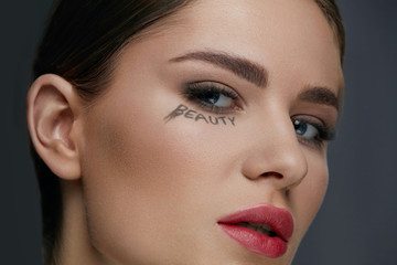Beauty face makeup. Woman model with make-up and word on skin