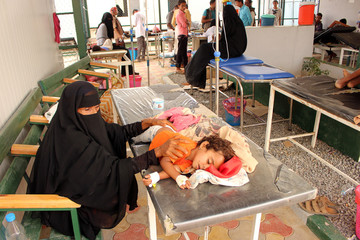 A girl, cholera patient, lies on a bed as she receives medical care at a health center in the village of Islim, in the northwestern province of Hajjah