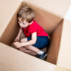 cute young child resting, playing in cardboard box for imagination
