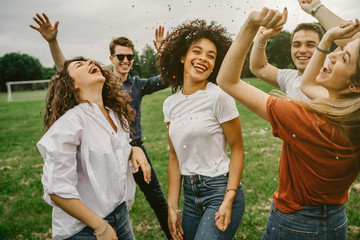 Group of five friends having fun at the park - Millennials dancing in a meadow among confetti thrown in the air - Day of freedom and carefree