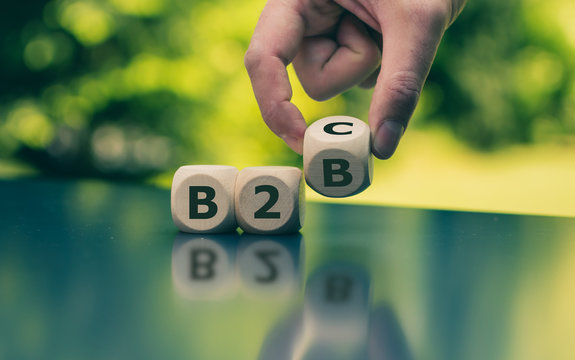 "Business to Business or Busness to Consumer? Hand turns a dice and changes the expression ""B2B"" to ""B2C"" (or vice versa)"
