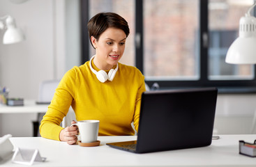 business, break and people concept - businesswoman with laptop computer drinking coffee at office