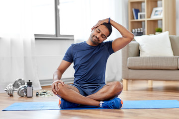 sport, fitness and healthy lifestyle concept - indian man training and stretching body at home