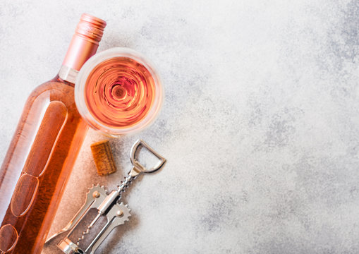 Bottle and glasses of pink rose wine with cork and corkscrew opener on stone kitchen table background. Top view. Space for text
