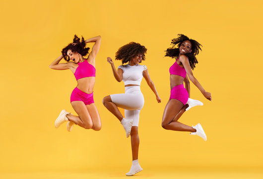 Three strong and happy athletic women, jumping or dancing on yellow background wearing color sportswear. Fitness and sport motivation.