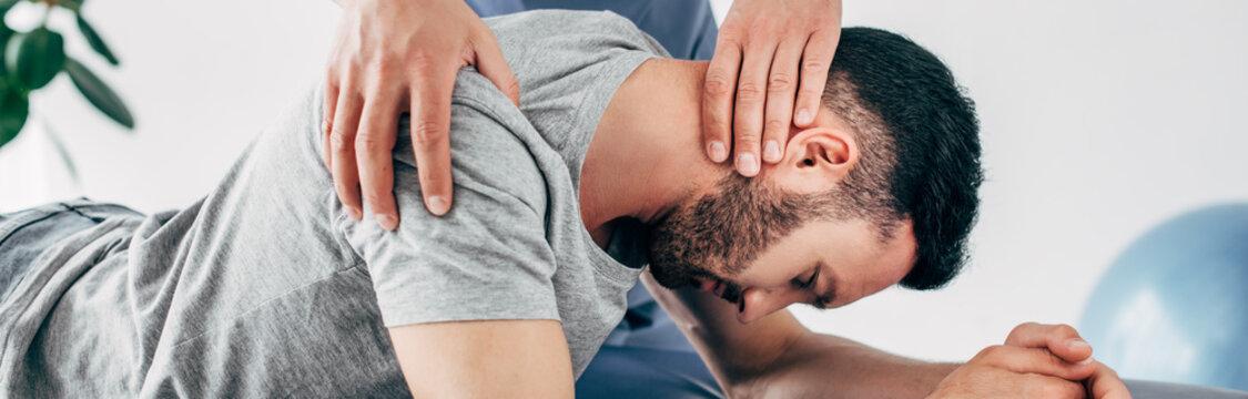 panoramic shot of chiropractor massaging neck of lying man
