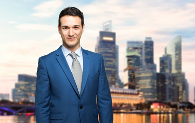 Businessman outdoor smiling with a modern skyline in the background