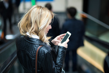Young blonde woman using her smartphone on an escalator in the subway