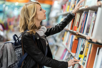 Woman searching for a book in a library