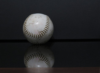 A horizontal photo of a baseball with a black background.