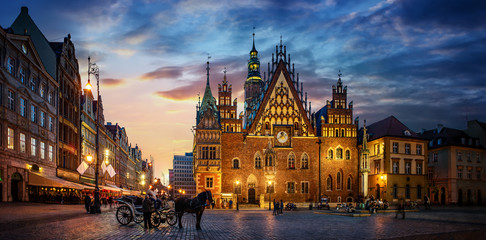 Wroclaw central market square with old houses, Town Hall and sunset, horse and carriage. Panoramic night view, long exposure. Historical capital of Silesia, Wroclaw (Breslau) , Poland, Europe.