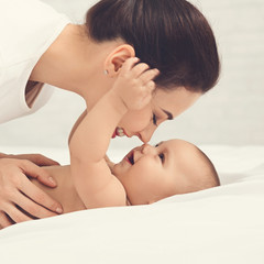 Mother playing with her baby in bedroom.