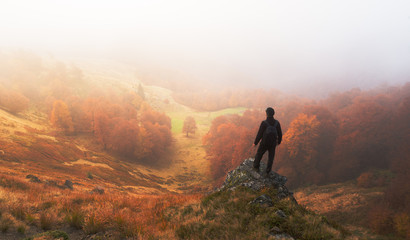Man stands on background of autumn landscape