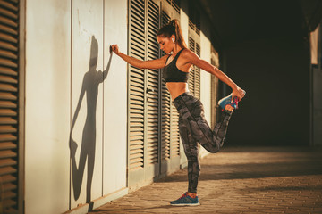 Young woman warming up and stretching legs before jogging