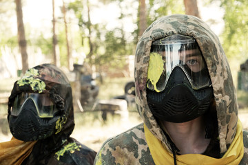 Summer. Paintball. Two players with a defeat in the head in a camouflage suit and a protective mask...
